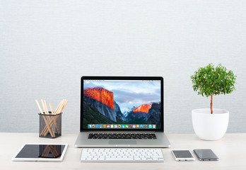 Photo of workplace with modern gadgets iPhone, ipad and Macbook Pro by Apple. Apple Inc. is an American multinational corporation that designs, develops, and sells consumer electronics.