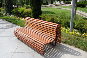 Beautiful comfortable wooden bench of brown slats with a smooth transition. Arrangement of the park comfortable places for recreation, a large wooden bench in the park in the city center.