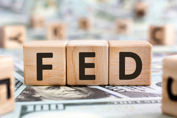 FED - acronym from wooden blocks with letters, abbreviation FED Federal Reserve System or federal agent concept, random letters around, money background
