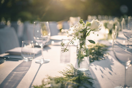 Beautiful outdoor table setting with white flowers for a dinner, wedding reception or other festive event.