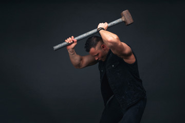 young bodybuilder in black clothes with a sledgehammer in his hands. Studio photography