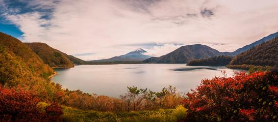 Landscape image of Mt. Fuji over Lake Motosu with autumn foliage at sunset in Yamanashi, Japan.
