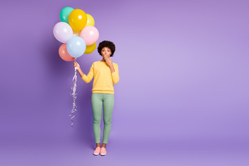Omg i share secret. Full length photo of amazed mulatto girl close mouth palm hold baloons tell news friends birthday celebration party wear green yellow outfit isolated violet color background