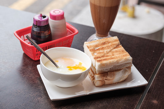 Kaya Toast, Coffee bread and Half-boiled eggs Singapore breakfast. Iced coffee and bread toast with a local jam made from eggs, sugar and coconut milk.