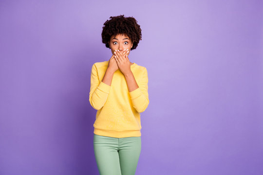 Photo of frightened horrified terrified girlfriend covering her mouth with hands after having told restricted private informaion wearing green pants trousers yellow sweater trendy stylish isolated