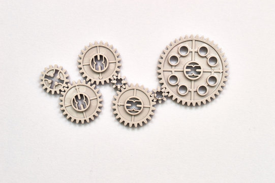 many plastic toy gear wheels connected to each other representing concept of team work and transmission on the paper background