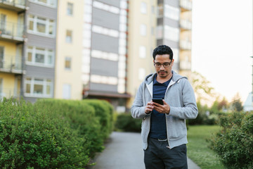Man using smart phone by apartment building