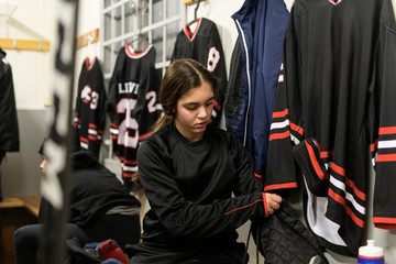 Girl in changing room prepares for ice hockey training
