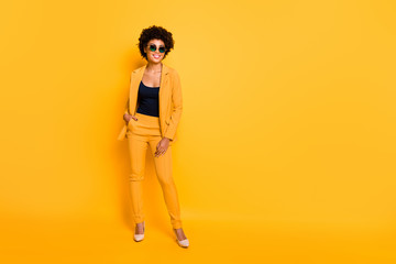 Full length photo of positive cheerful afro american have rest relax feel fun dream dreamy put hands in trousers wear stylish suit high-heels isolated over yellow color background