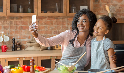 Cheerful mom and daughter taking selfie while cooking at kitchen