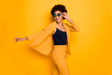 Profile side photo of positive cheerful afro american girl have rest relax look enjoy fall holidays wear fashionable vogue suit isolated over yellow color background