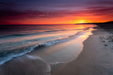 Sunrise at sandy beach in Baabe, slow incoming waves, morning sky with orange sunrise, Ruegen island, Baltic Sea, Germany.