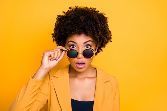 Close-up portrait of her she nice attractive pretty lovely shocked speechless wavy-haired girl touching specs staring eyes isolated over bright vivid shine vibrant yellow color background