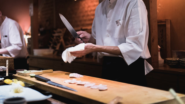 Chef wiping knife, motion. Omakase style Japanese traditional.