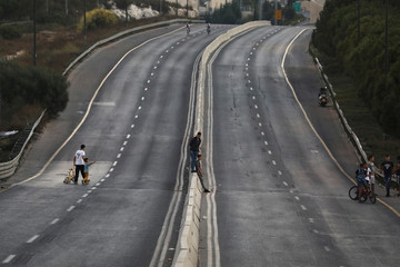 People ride their bicycles on an empty main road during the Jewish holiday of Yom Kippur in Jerusalem