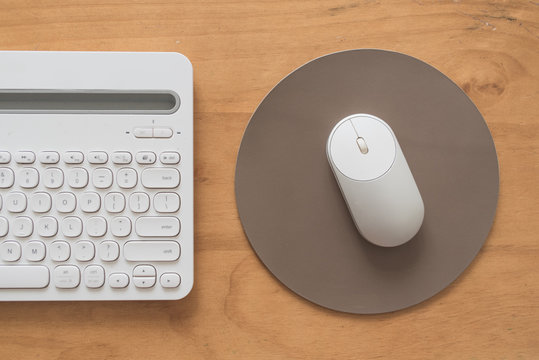 White and silver wireless mouse on a gray round leather mouse pad on a wooden surface with a keyboard beside