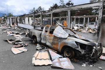 A car burned in September's riot is pictured at damaged office building of Jayawijaya's regent in Wamena