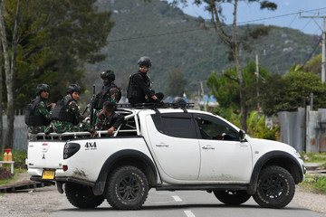 Indonesian soldiers and police officers sit on a car as they patrol in Wamena