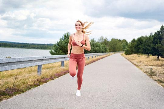 Smiling athletic woman jogging near lake