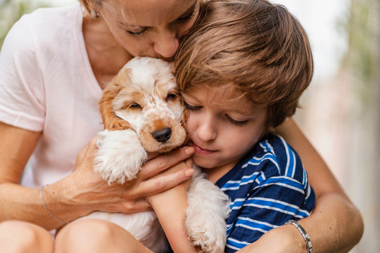 Mother snd son cuddling with cute dog puppy