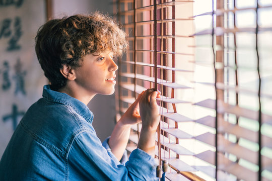 Boy at the window looking through blinds at home