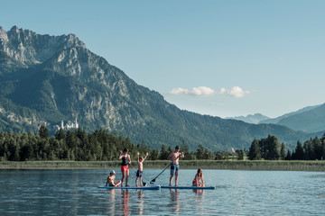Family with stand up paddle boards on a lake, Bannwaldsee, Allgaeu, Bavaria, Germany