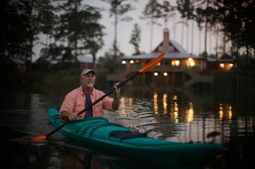 Mature man smiling while kayaking.