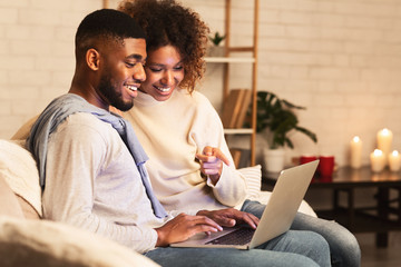 Loving afro couple choosing film on laptop, resting in cozy room
