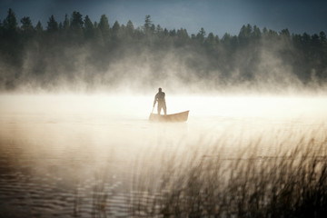 man standing in canoe in foggy lake