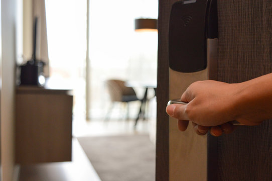 Female hand opening four-star hotel room