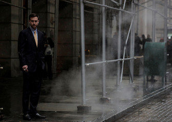 A man smokes a cigarette on Wall St. in New York