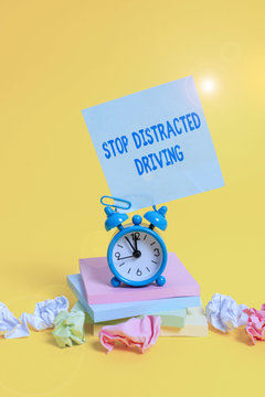 Text sign showing Stop Distracted Driving. Business photo showcasing asking to be careful behind wheel drive slowly Alarm clock sticky note paper balls stacked notepads colored background