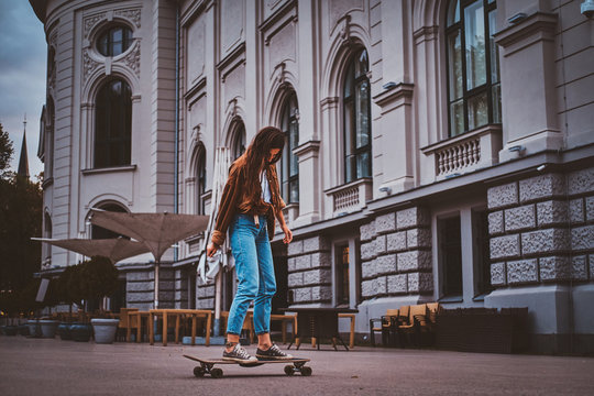 Skater girl in denim is riding her longboard on the street.