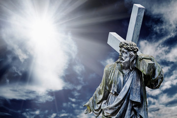 Dramatic image of the crucifixion of Jesus Christ in the rays of light. Ancient statue.