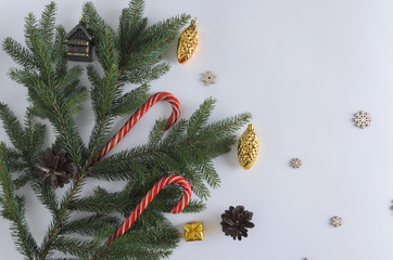 A Christmas tree branch lies on a white background, Christmas toys hang on a branch - golden cones, red Christmas candy canes, cones and wooden snowflakes