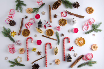 Christmas and New Year decorations lie on a white background: fir branches, lollipops, candles, dried orange, dried apples, cinnamon sticks, anise stars, cones, wooden stars, Christmas toys, cotton.