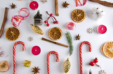 CNew Year attributes on a white background. Dried oranges, cinnamon, anise, Christmas tree twigs, candy canes, red candles, tinsel, wooden snowflakes, cotton.