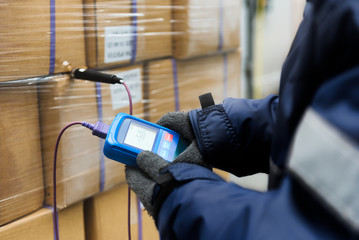 Obraz Hand of worker using thermometer to temperature measurement in the goods boxes with ready meals after import in the cold room or warehouse for keep temperature room - fototapety do salonu