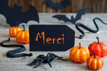 Black Label With French Text Merci Means Thank You. Scary Halloween Decoration Like Bat, Snake And Spider