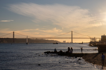 People taking pictures near the river Tagus in Lisbon with the 25th of April Bridge in the background.