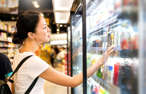 Portrait of caucasian woman looking at product at grocery store. Happy hispanic girl shopping in supermarket reading product information. Costumer buying food at the market, woman lifestyle concept.