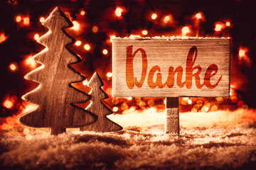 Wooden Sign With German Calligraphy Danke Mean Means Thank You. Christmas Tree On Snow And Fairy Lights In Background. Red Spotlight With Snowflakes