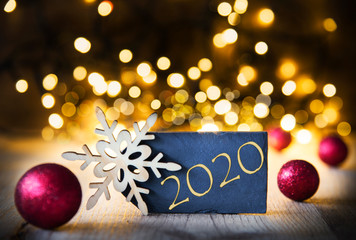 Plate With Golden Text 2020 For Happy New Year Greetings. Bright Glowing Lights In The Background. Christmas Ornament Like Red Balls And Snowflake.