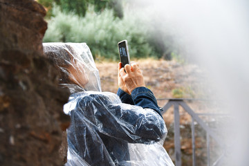 Woman taking pictures using cell phone in the rain