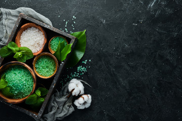 Green sea salt in a bowl. On a black stone background. Spa treatments. Top view. Free space for your text.