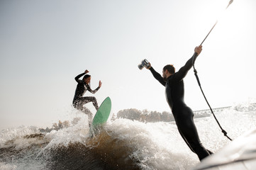 Photographer taking extreme pictures from the motorboat of the girl riding on the wake surf