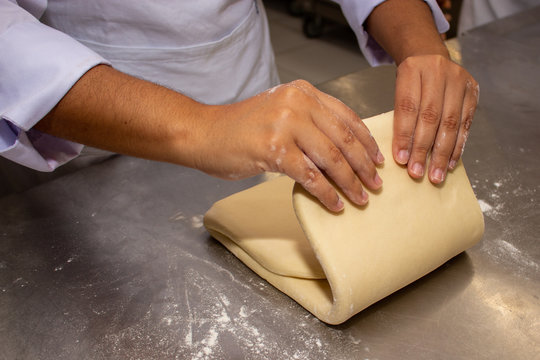 Chef hands making and folded raw puff pastry. Making puff pastry.   on a stainless steal table. First step, dough and the butter on the table.Close up. pastry chef. how to make.