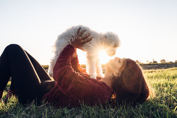 Young and beautiful woman playing with her little poodle dog at the park at sunset