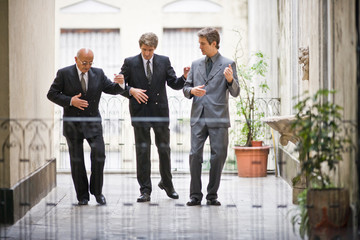 Senior business man teaching two mid-adult male colleagues to dance on a balcony.