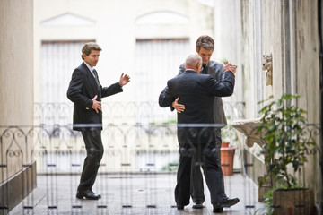 Senior business man teaching a mid-adult male colleague to dance while another male co-worker follows on a balcony.